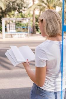 外で本を持って読んでいる女性