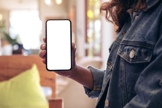Женщина, держащая и показывающая черный мобильный телефон с пустым белым экраном на столе в современном кафе