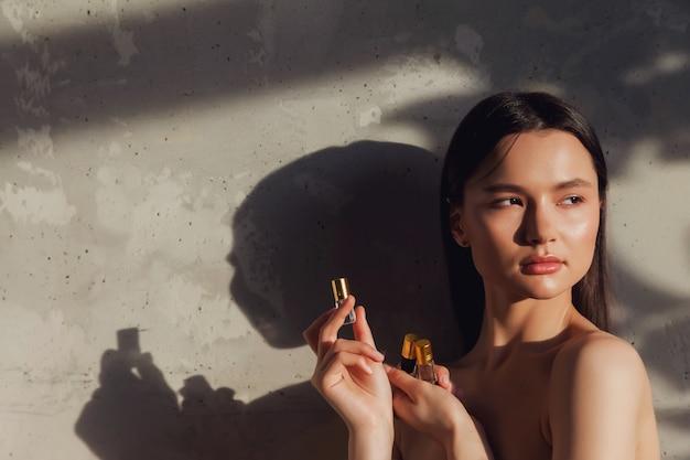 葉の陰で古い壁の背景に化粧品の香水瓶を保持し、表示する女性。美容治療のコンセプト。広告のコンセプトは健康的なライフスタイル、spa、セルフケアです。コピースペース