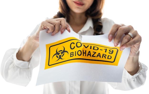 코비드-19 생물학적 위험 단어로 종이를 들고 찢는 여자. 코로나리부스에서 마무리하고 회복한 후 행복과 웰빙에 대한 아이디어 또는 개념.