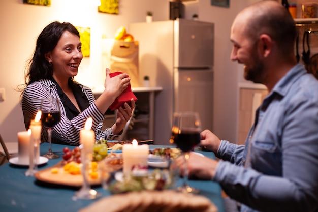 夕食時に夫からの記念日の贈り物を保持している女性。結婚記念日を祝う食事を楽しみながら、家で一緒に食事をする幸せな陽気なカップル。