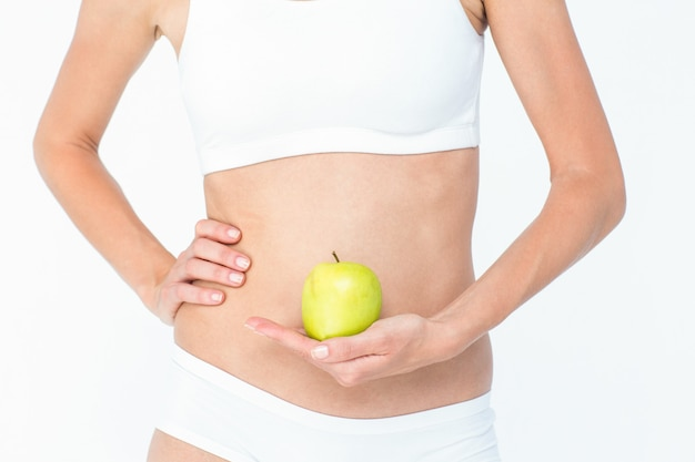 Woman holding an apple in front of her belly