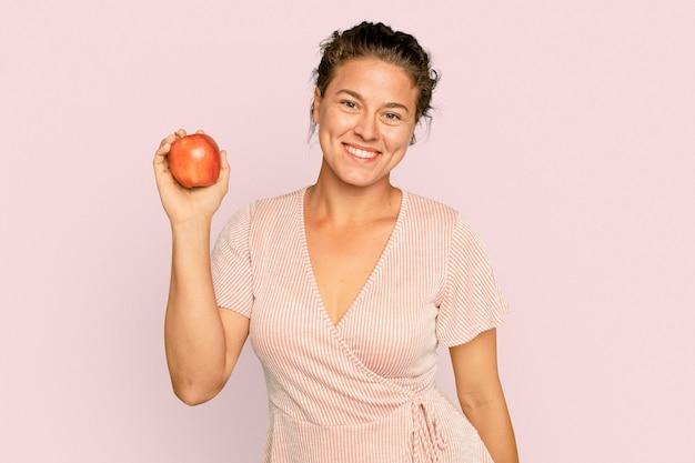 Donna che tiene la mela per la campagna di un'alimentazione sana