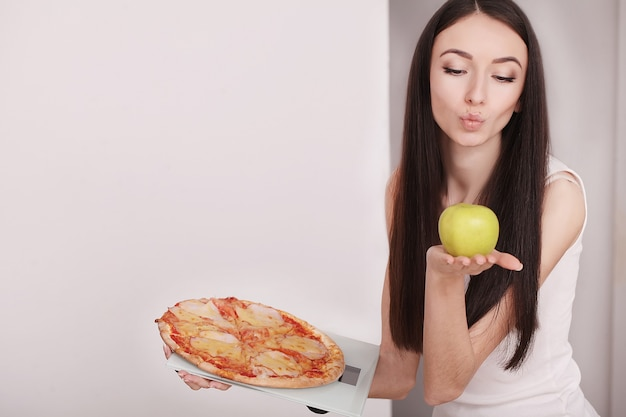 リンゴ、体重計、ピザを持っている女性