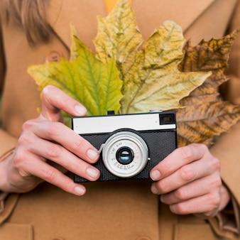 Foglie di autunno della tenuta della donna e la sua macchina fotografica