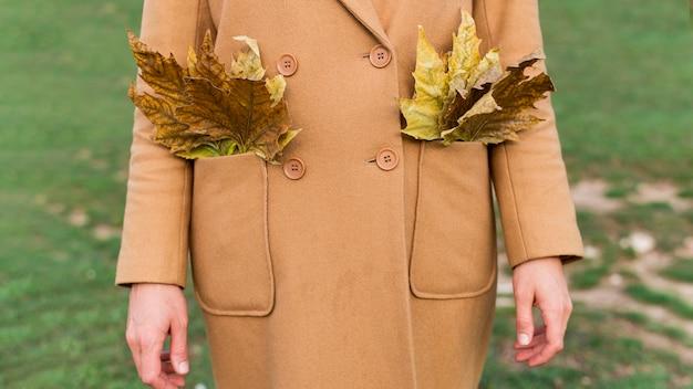 Женщина, держащая осенние листья в ее карманах