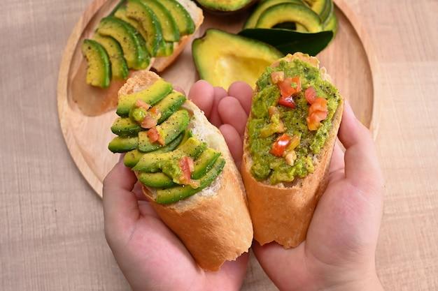 Woman holding avocado sandwich for breakfast.