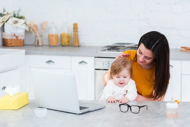 Woman holding baby in the kitchen with laptop