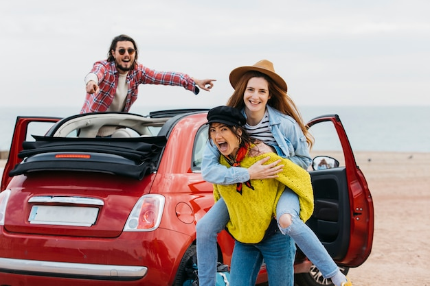 Woman holding on back happy lady near man leaning out from car