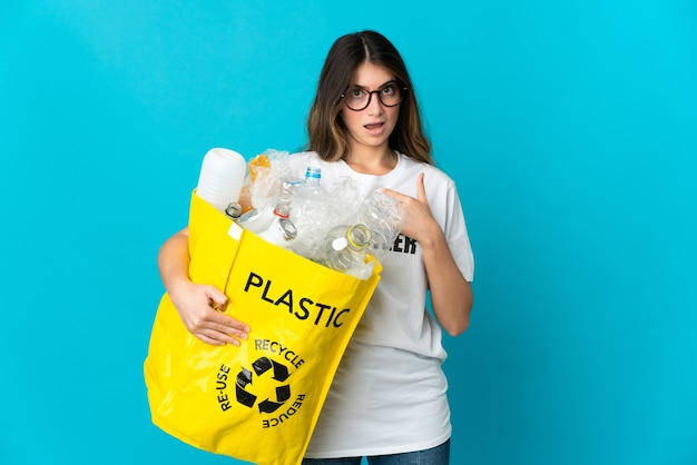 Woman holding a bag full of bottles to recycle on blue with surprise facial expression