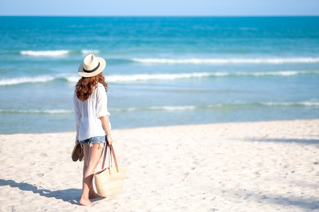 A woman holding bag and shoes while strolling on the beach with the sea and blue sky background