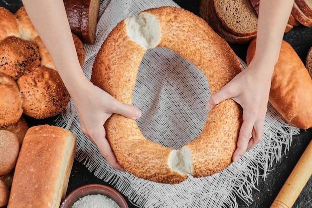 さまざまなパンと暗いテーブルにベーグルを保持している女性。