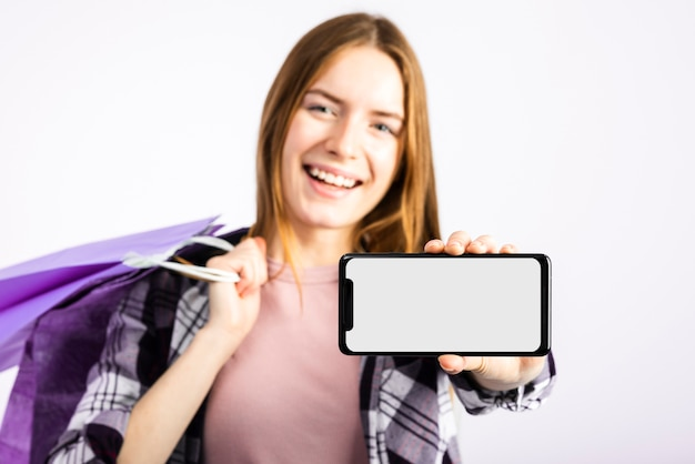 Woman holding bags and showing phone at camera