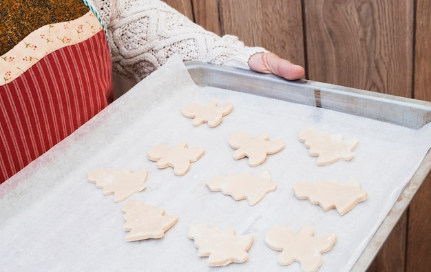 Woman holding baking sheet with christmas cookies