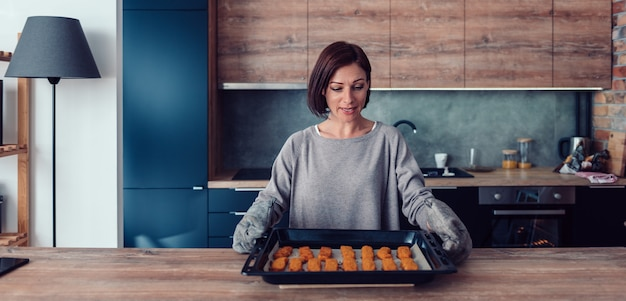 Woman holding baking tray with backed chicken nuggets