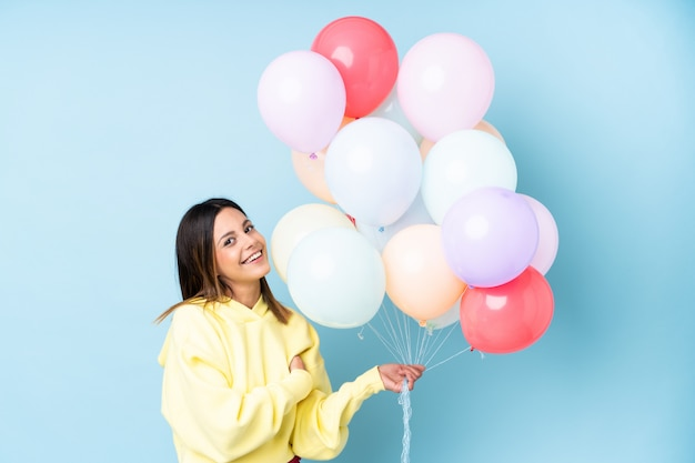 Woman holding balloons in a party over isolated blue wall laughing