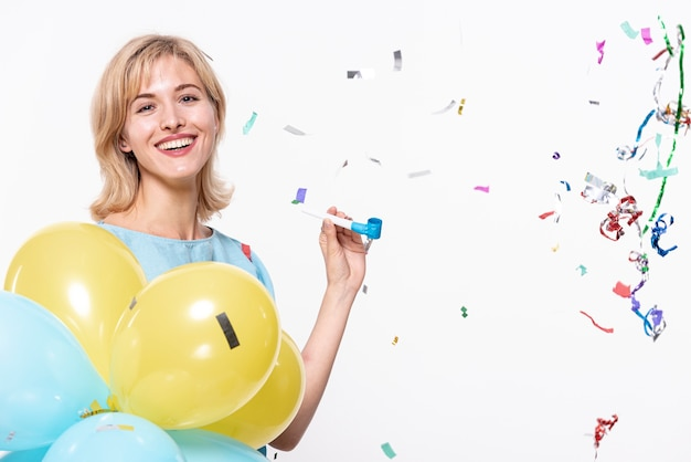 Woman holding balloons surrounded by confetti