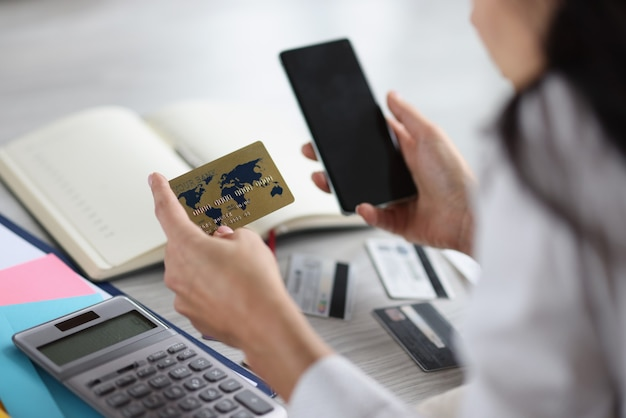 Woman holding bank credit card and phone in her hands. payment of bills concept