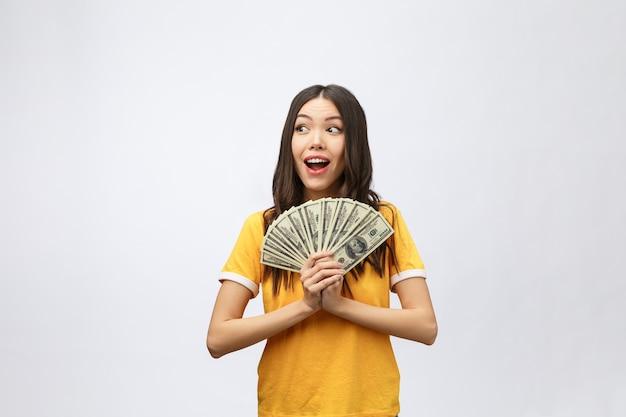 Женщина, держащая банкноту деньги. довольно молодая модель показывает наличные деньги