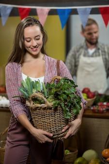 식료품가 게에서 녹색 잎이 많은 채소 바구니를 들고 여자