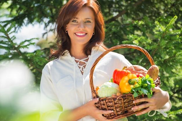 Женщина, держащая корзину овощей