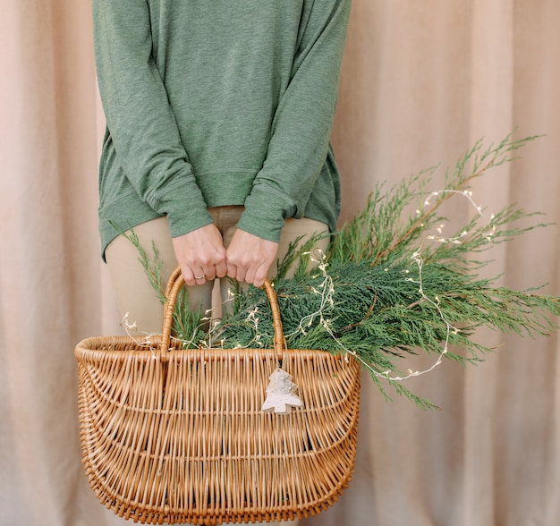 Woman holding a basket with christmas needles and a symbol wooden toy deer