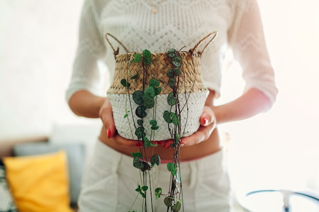 Woman holding basket with string of hearts at home.