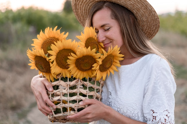 Woman holding basket with sunflowers