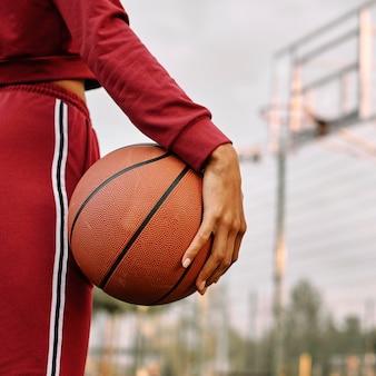 Donna che tiene un pallone da basket accanto alle sue gambe