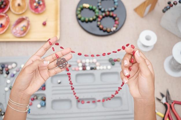 Женщина держит красивое ожерелье