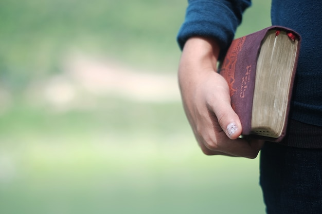 Woman holding a bible book.