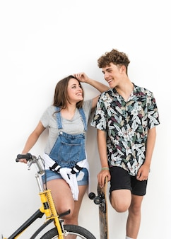 Woman holding bicycle and man holding skateboard looking at each other