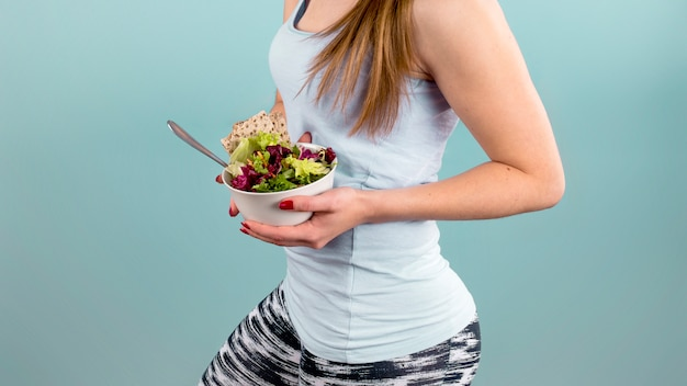 Woman holding big bowl with vegetable salad in hands