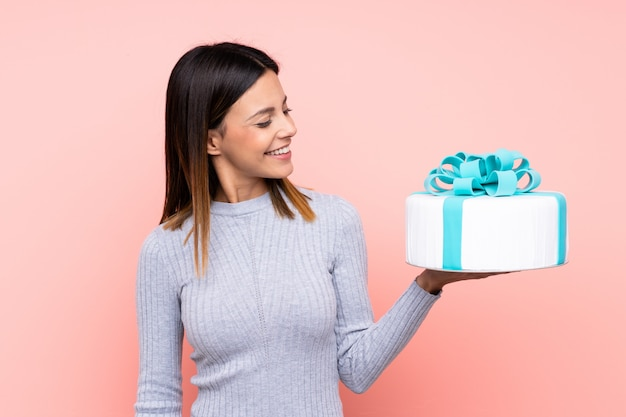 Woman holding a big cake over isolated pink wall with happy expression