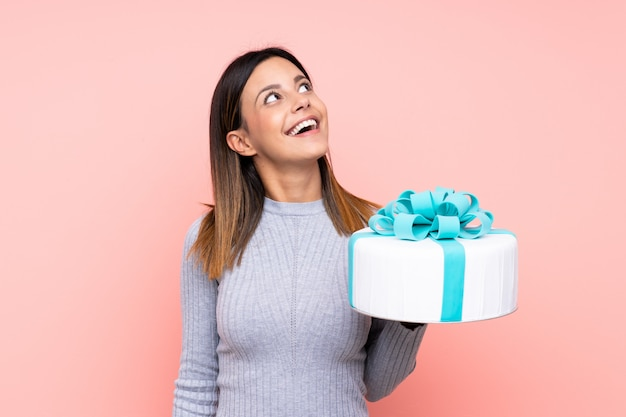 Woman holding a big cake looking up while smiling