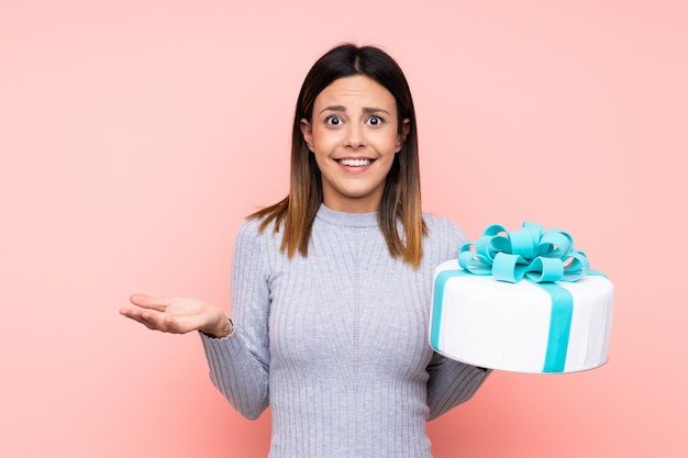 Woman holding a big cake over pink wall with shocked facial expression