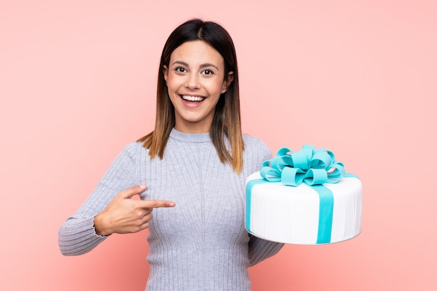 Woman holding a big cake over pink wall with surprised facial expression