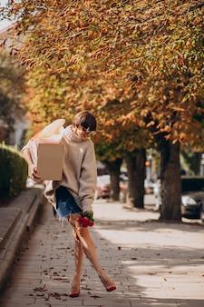 大きな小包ボックスを持って通りを歩いている女性