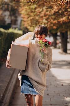 Женщина держит большую посылку и гуляет по улице