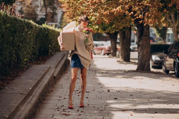 Donna che tiene grande cassetta dei pacchi e camminare in strada