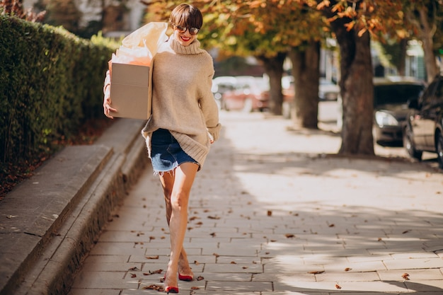 Woman holding big parcel box and walking in the street