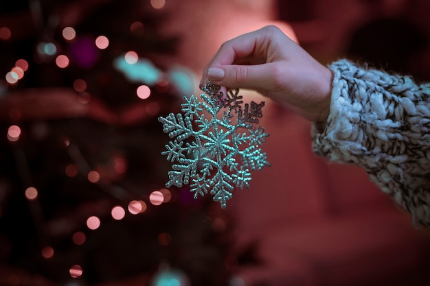 Woman holding big snowflake in hand