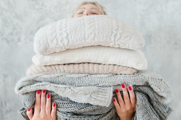 Женщина, держащая большой стек связанных пледов и одеял. уютный и теплый зимний домашний декор