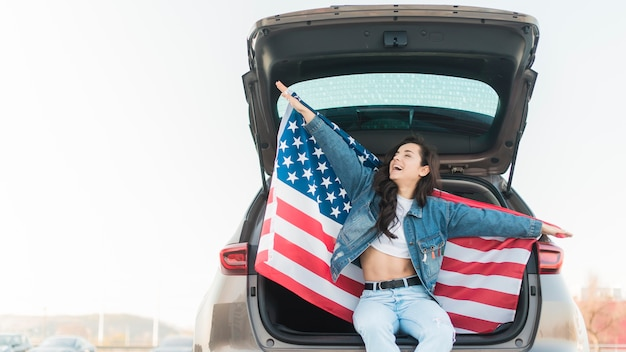 Woman holding big usa flag in car trunk