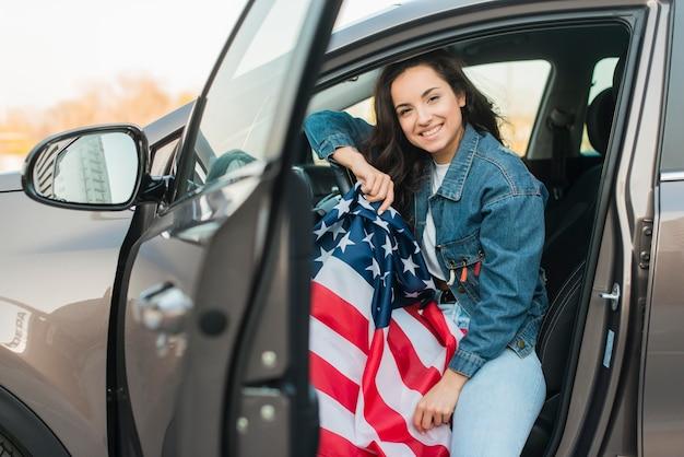 Женщина держит большой флаг сша в машине