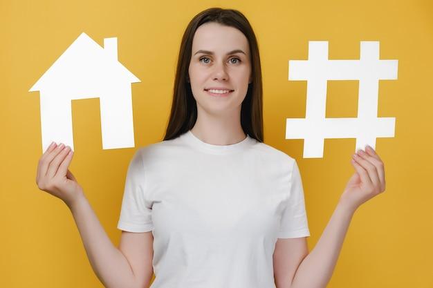 큰 흰색 해시태그와 집 모델을 들고 있는 여성