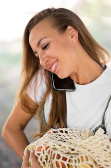 Woman holding a biodegradable bag with goodies while talking on the phone
