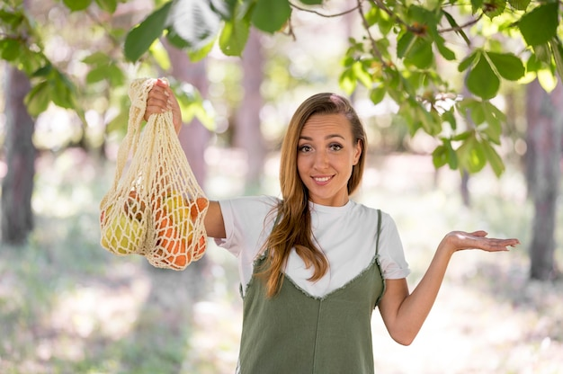 Woman holding a biodegradable bag with vegetables and fruits