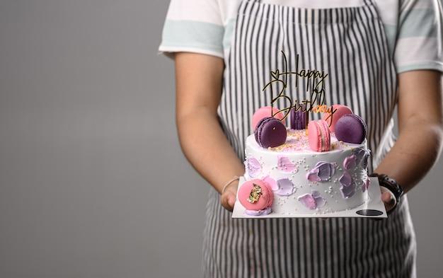 Woman holding birthday cake with macarons