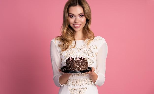 Donna che mantiene una torta di compleanno